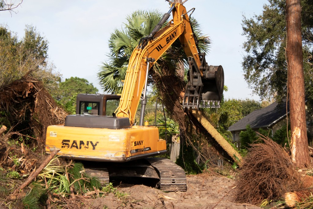 Tractor tearing down a palm tree